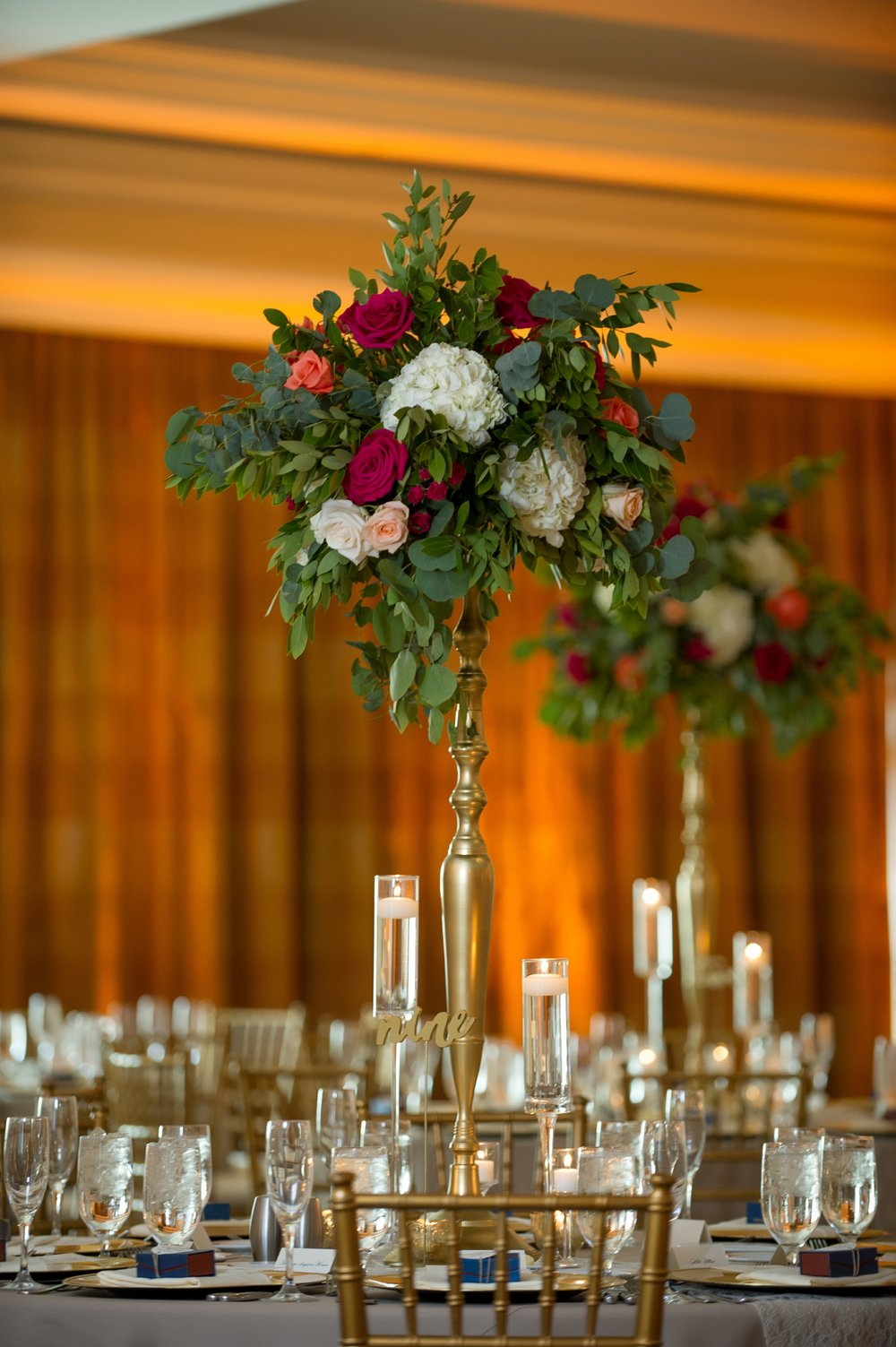 Floating candles and gold table numbers sat beneath gold pillar vases overflowing with greenery and florals.