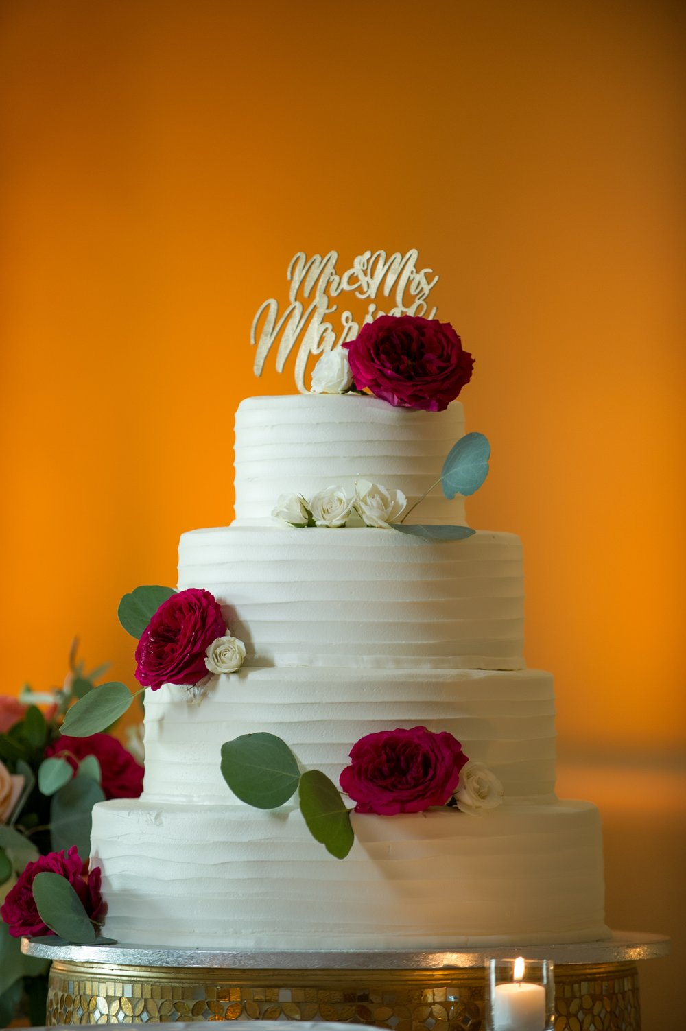 The couple chose a beautifully classic white four tiered cake, decorated with textured icing, luscious florals, and finished off with a custom gold topper.