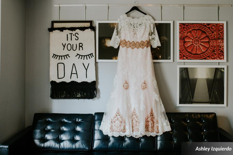 Having trouble finding a unique dress she loved, the bride bought a traditional wedding dress and had a seamstress modify it with custom blush tulle underlay and bronze appliqués.