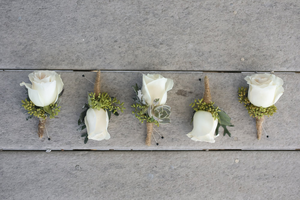 The boutonnieres reflected the clean color palette and unique succulent accents of the floral arrangements.