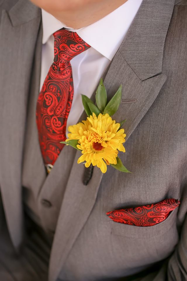 A yellow chrysanthemum boutonniere provides a harvest touch to the groom's look for this October wedding.