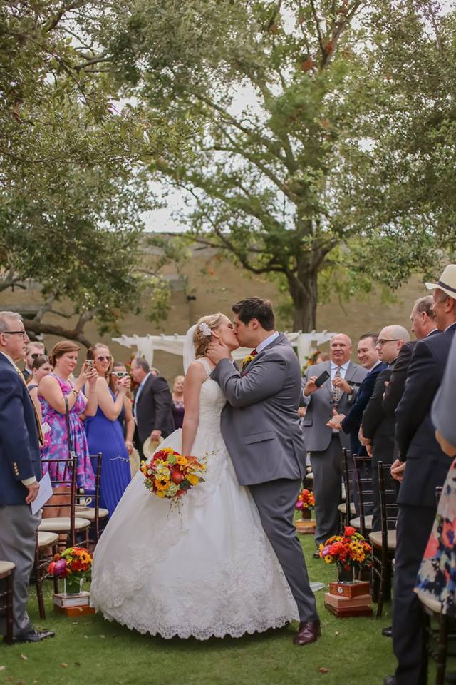 "The fairy tale couple share a kiss as they are received by guests, after saying ""I do""!"