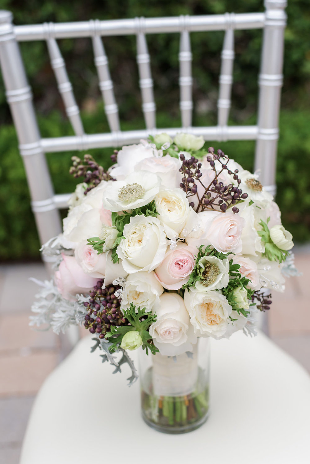 The bride's bouquet boasted garden roses, anemones, dusty miller, and berries.