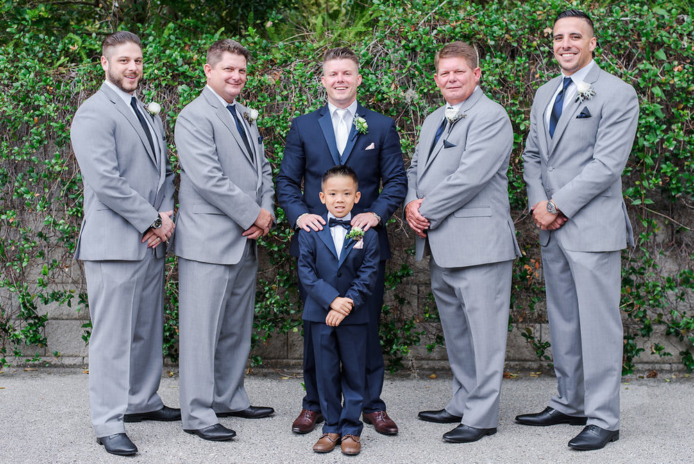 Groomsmen wore grey suits with navy accents, while the groom and ring bearer sported dapper navy suits with blush accents, to reflect the silver, navy, and blush color scheme.