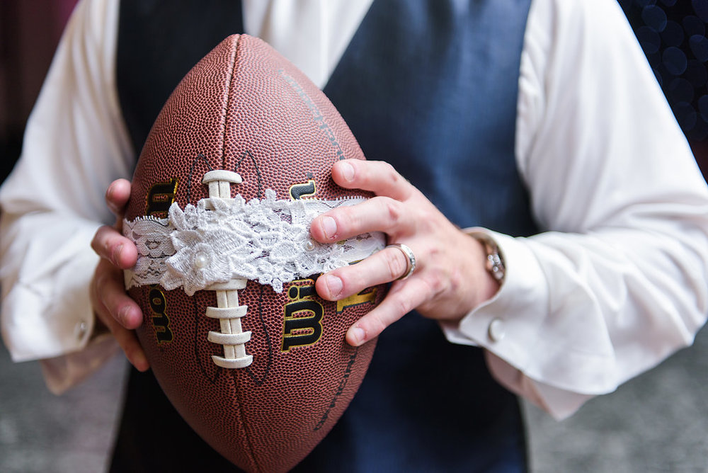 The garter was wrapped around a football to toss into the crowd of bachelors as a fun and unique version of this wedding tradition.