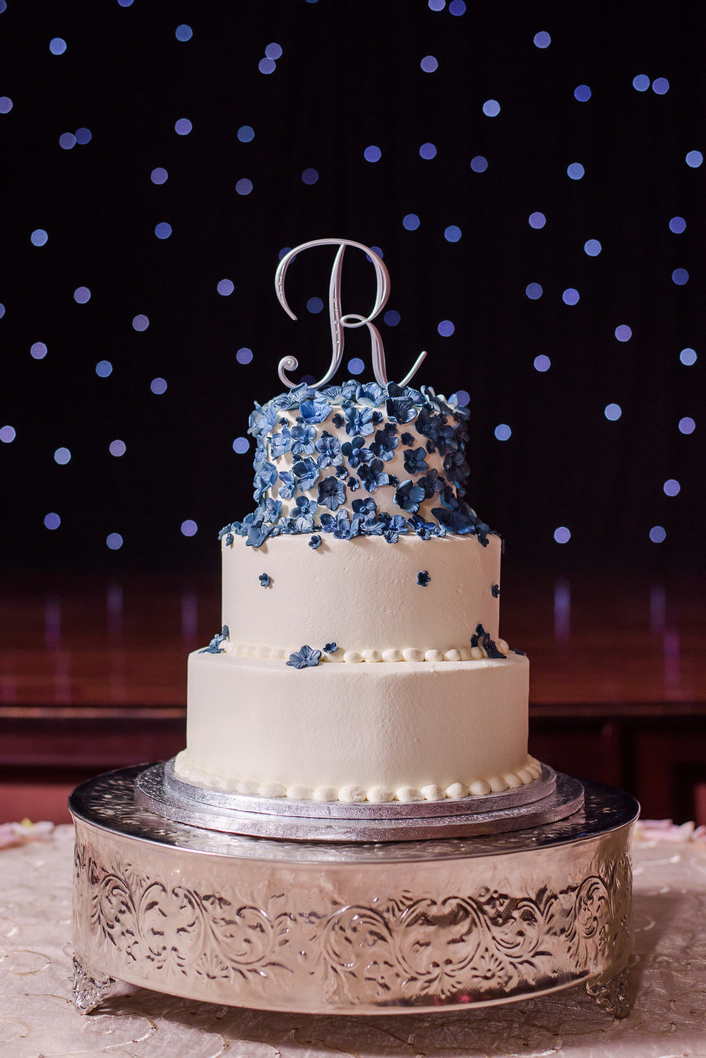 Blue sugared flowers cascaded down the simple and elegant three tier cake.