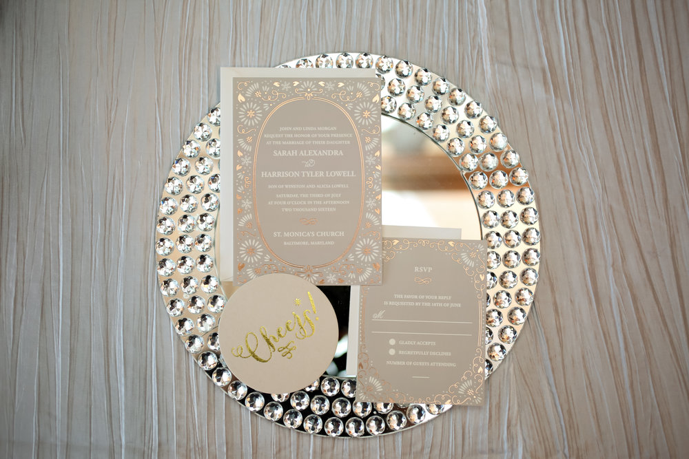 Metallic details in the invitation suite complimented the rhinestone and mirror chargers and mirror tabletops.