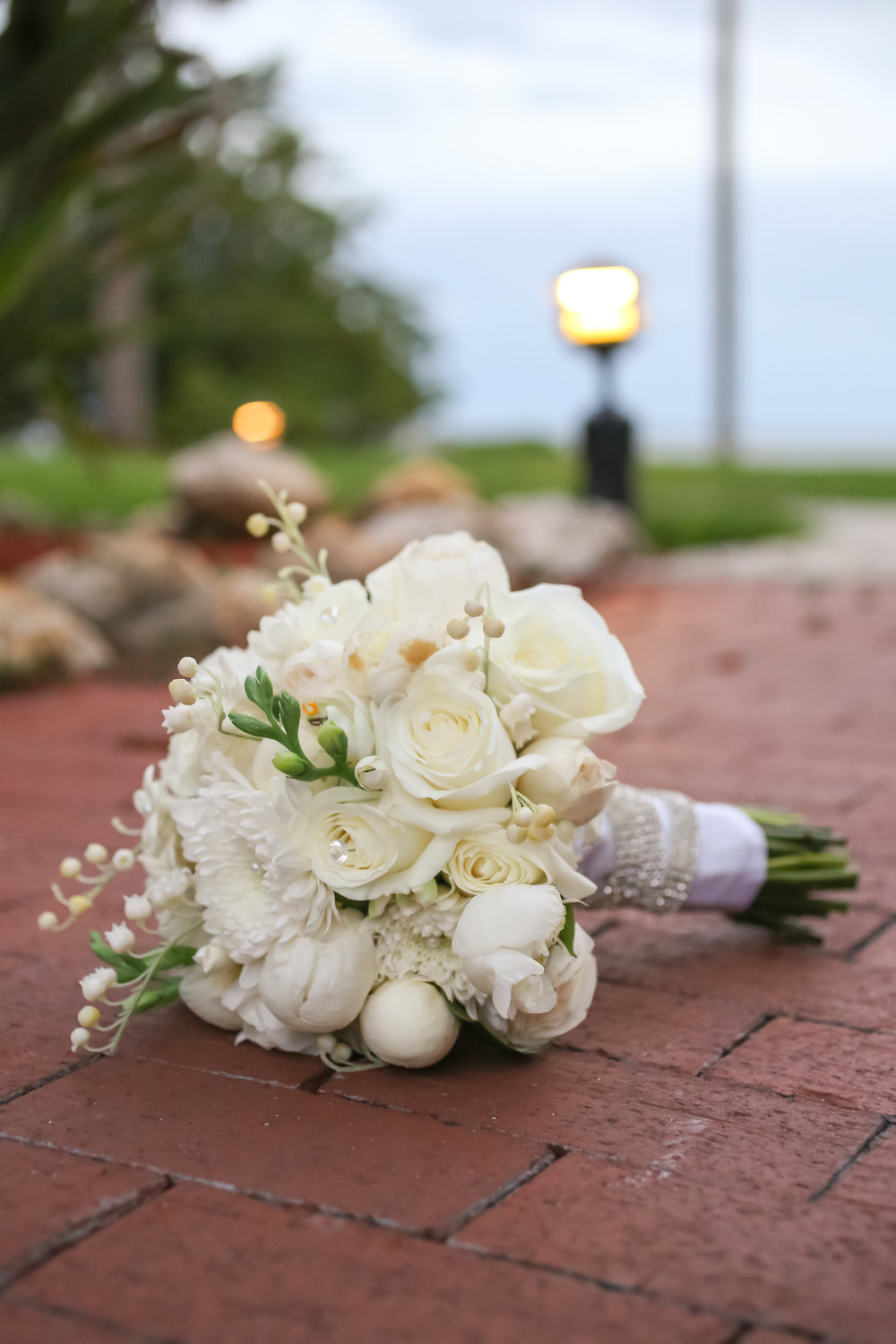 An ivory and white bouquet made up of roses, peonies, and berries was accented with rhinestones.