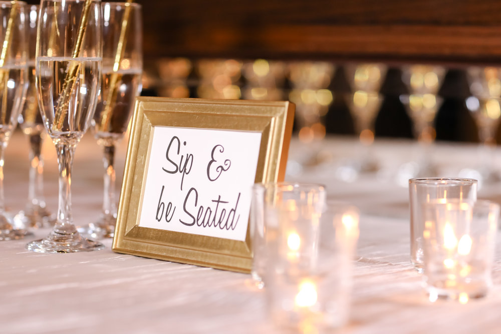 A champagne escort card display invited guests to 'Sip and Be Seated!'