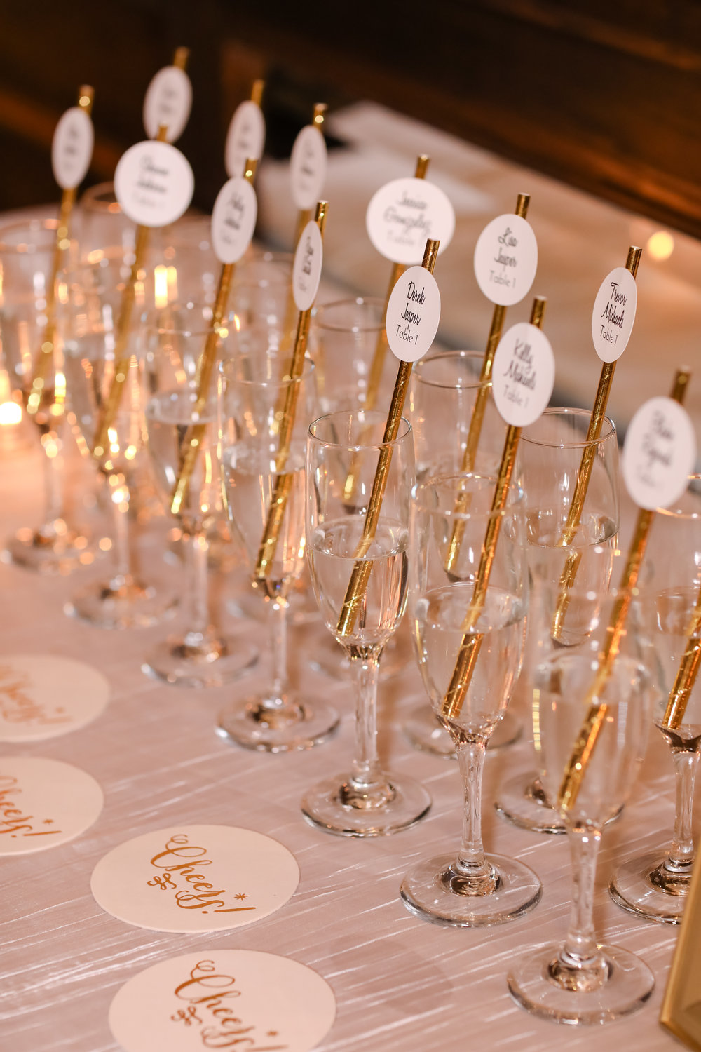 Glamorous gold paper straws featured printed escort cards inside glasses of sparkling champange!