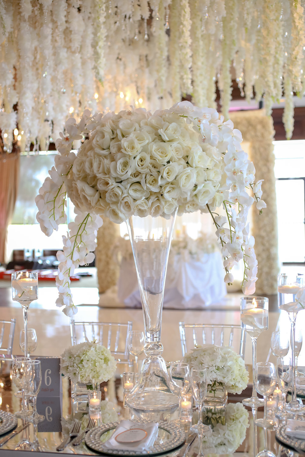 Ornate vases topped with fluffy hydrangea, rose, and dripping orchids sat amongst floating candles and crystal stemware.