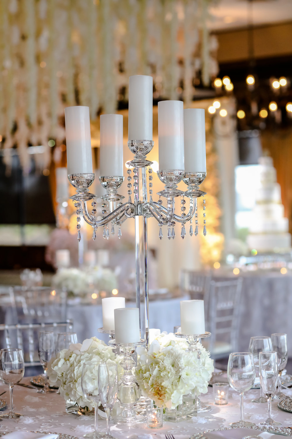 Alternating tables were topped with crystal candelabras, accented by floral arrangements and votives.