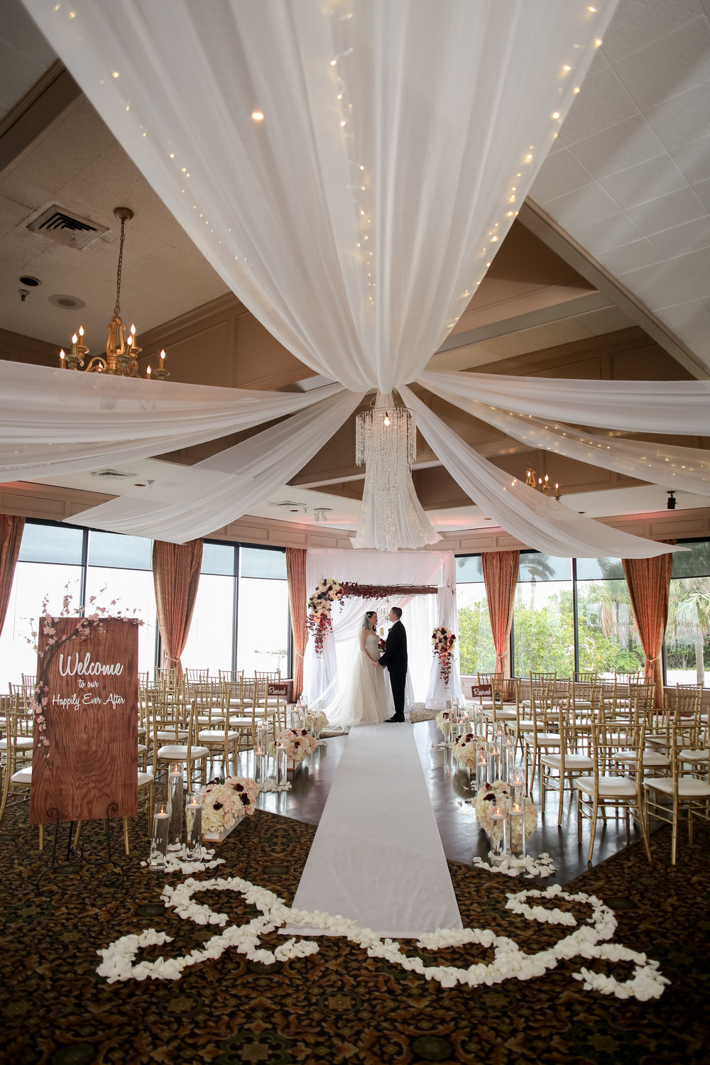 The ceremony space featured a stunning blossom branch arch with crystal chandelier and gold chiavari chairs facing floor-to-ceiling windows of the water.