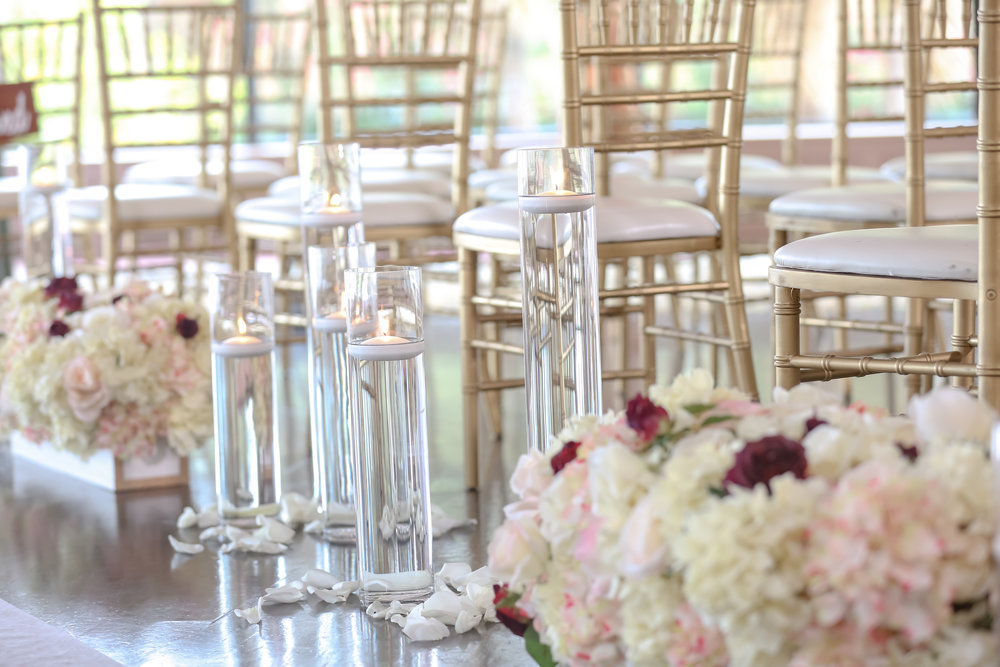 The ceremony aisle was lined with floating candles, rose petals, and lush flora in white hedge boxes.