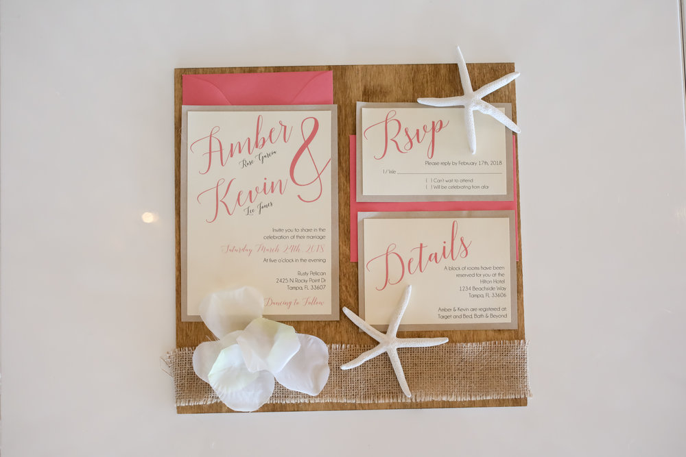An invitation suite featuring pops of coral give a hint to the theme of this wedding without being too 'beachy'.