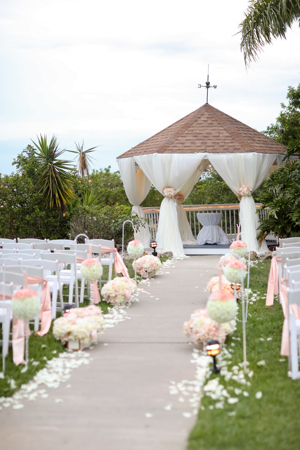 An intimate ceremony space overlooking the water featured pomander balls dripping with crystals, and a gazebo chandelier.