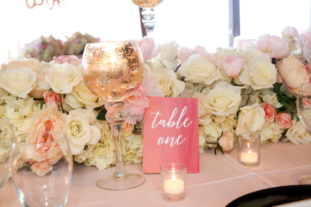 Lush florals were accented with the twinkle of gold and candlelight, and coral watercolor table numbers.