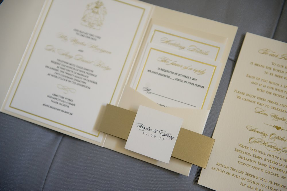 A classic pocket style invitation suite in coordinating colors featured gold accents and script calligraphy.