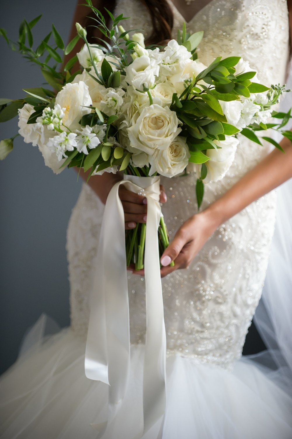 The bride carried a bouquet made of ivory roses, lisianthus, garden roses, stock, and greenery.