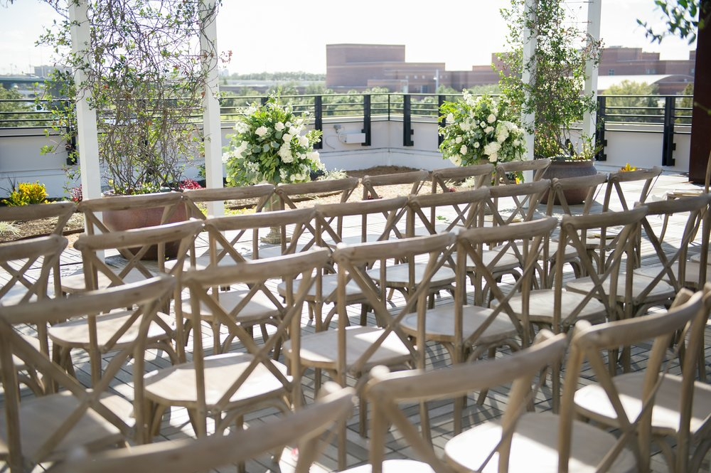Natural wood chairs adored the rooftop ceremony space to compliment the natural florals and greenery accents.