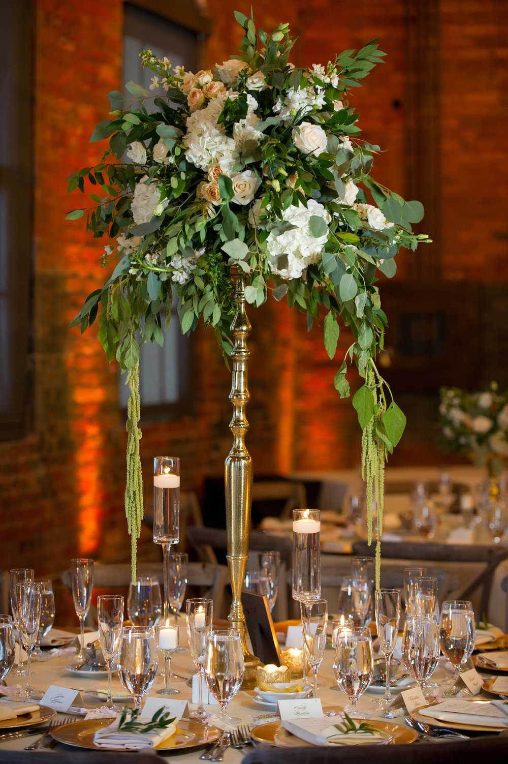 Arrangements of hanging amaranthus, ruscus, eucalyptus, hydrangea, stock, and roses towered over tables on opulent gold pillars.