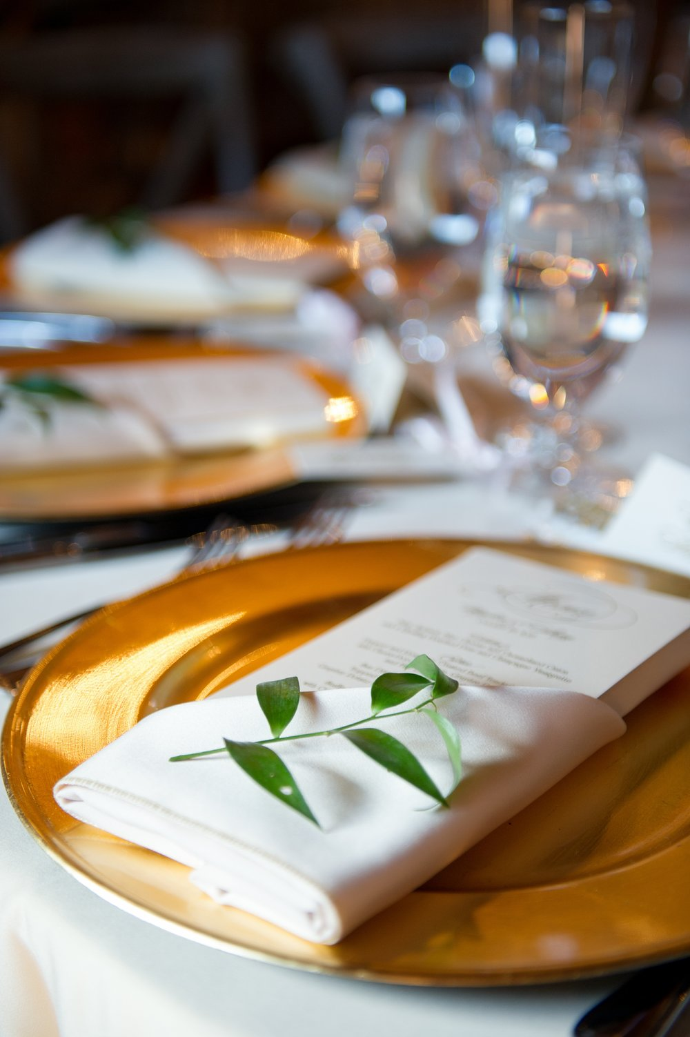 Tables were set with coordinating script menu cards tucked into napkins atop gold chargers, with sprigs of greenery at each place setting.