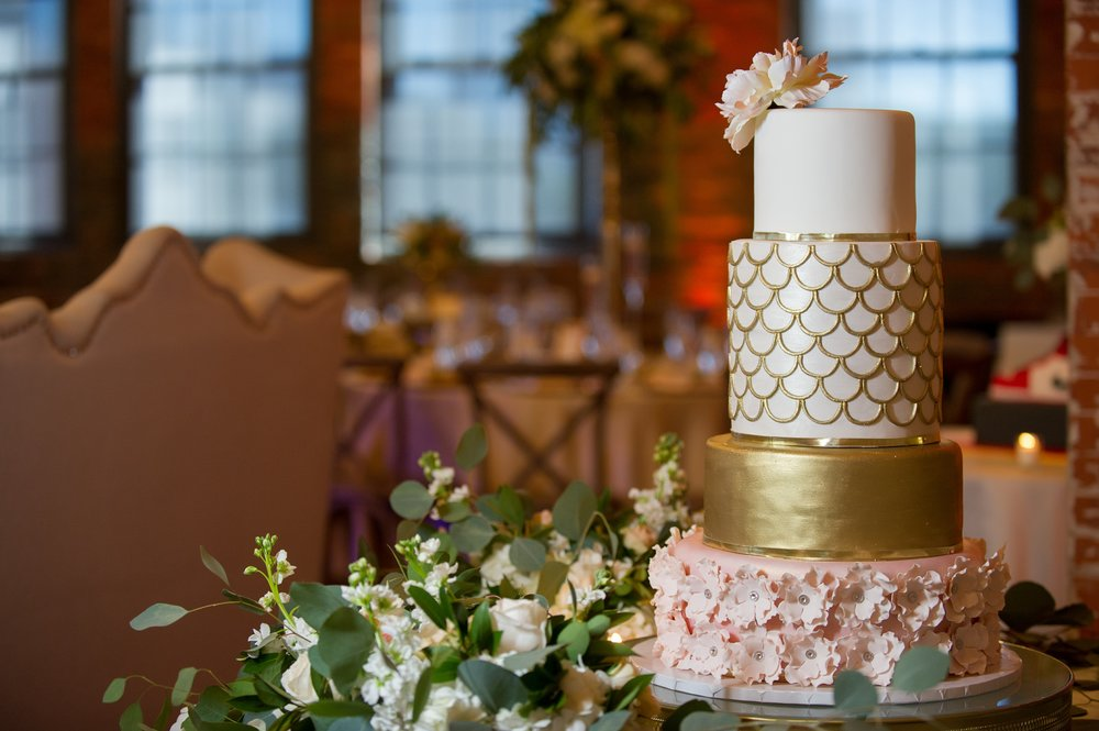 A stunning four tiered cake with gold and sugar flower details was surrounded by more flowers and greenery.