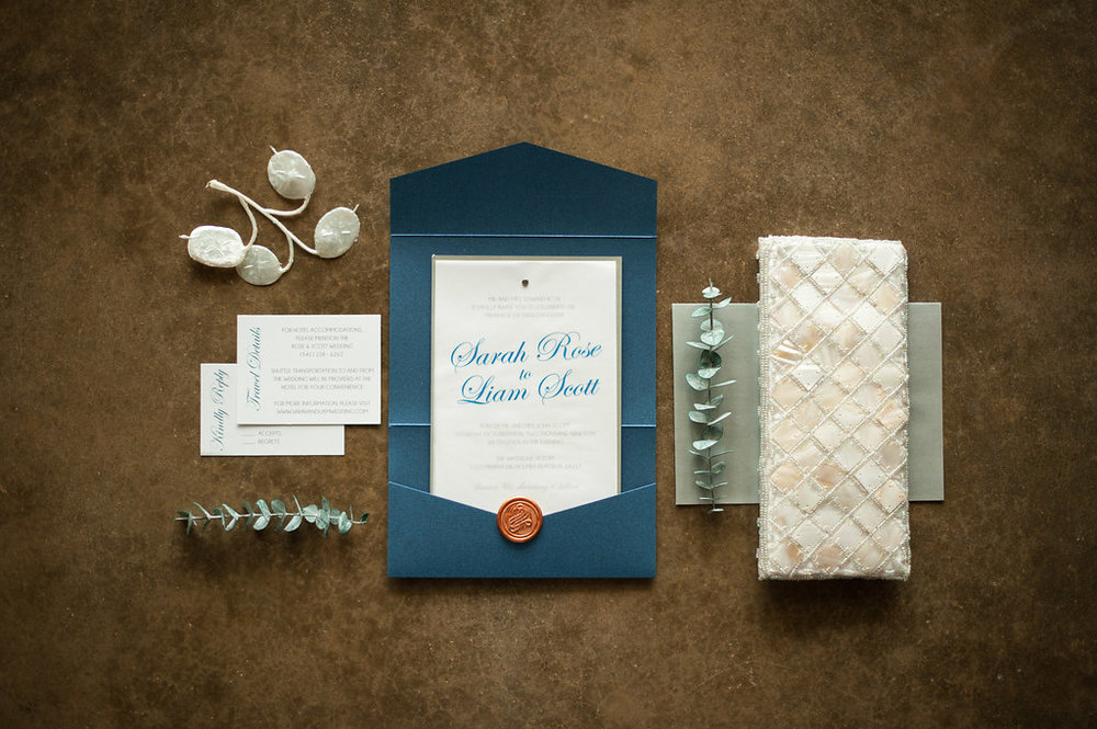 Fun invitations, with elegant script writing, in a range of shades of cobalt, dusty-blue, sage green, and ivory create a watery motif that perfectly sets the tone for this elegant beach wedding.