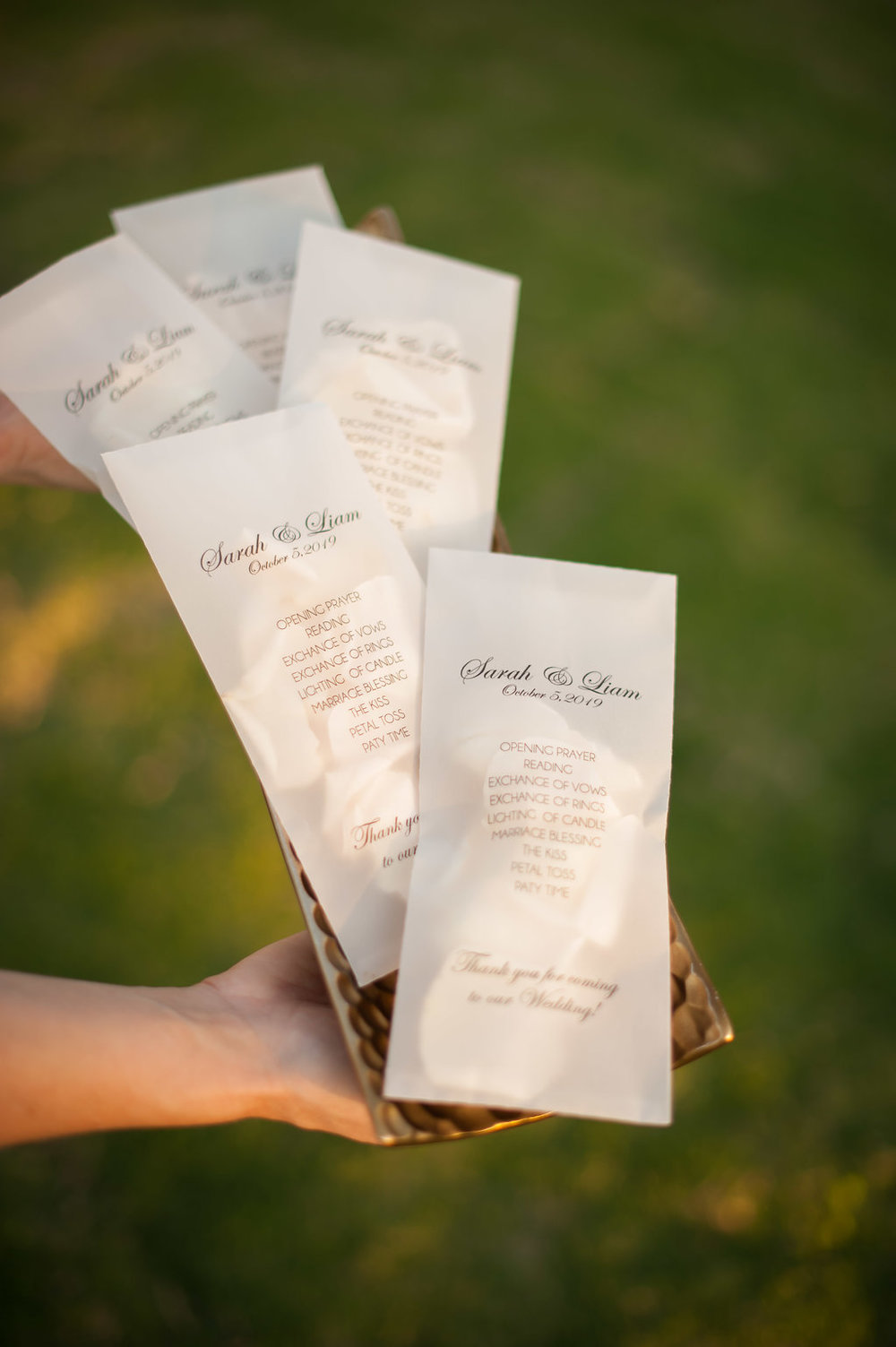 Glassine envelopes, printed with the program, were filled with ivory rose petals and handed out during the ceremony to use during the send off of the couple.