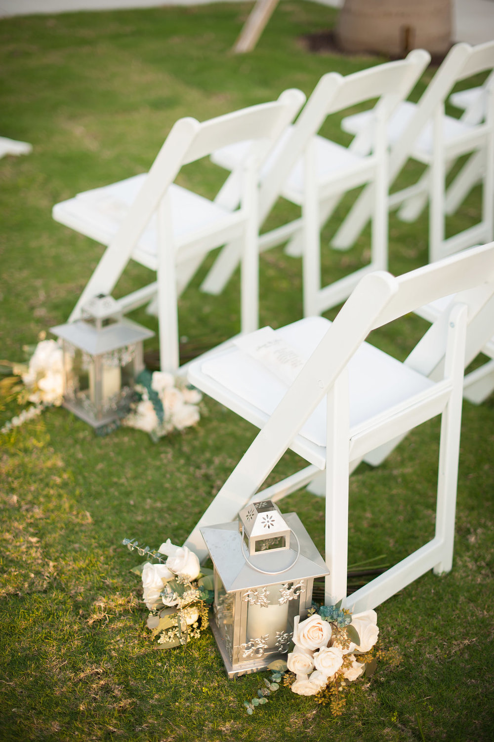 Silver lanterns and ivory florals, with pops of blue and green, lined the aisle.