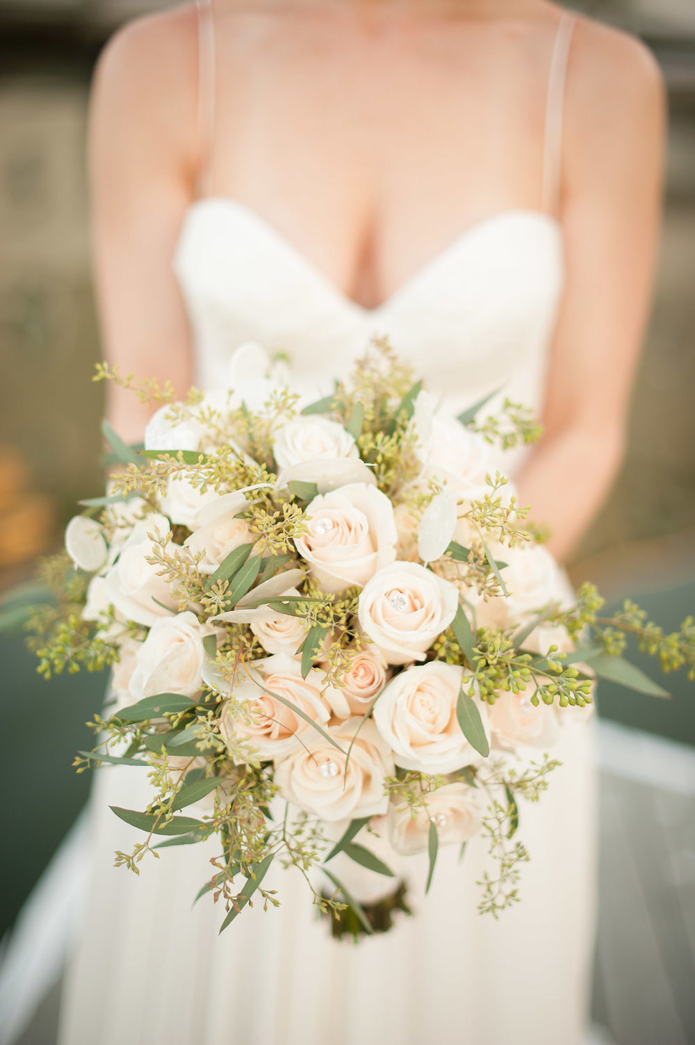 The bride's bouquet was kept simple and sophisticated with all ivory roses, greenery, and mother of pearl branches to resemble shells.