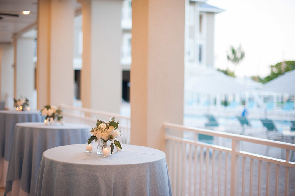 Soft blue and white burlap linens were paired with clusters of florals and candle light, on tables overlooking the waterfront pool, during cocktail hour.