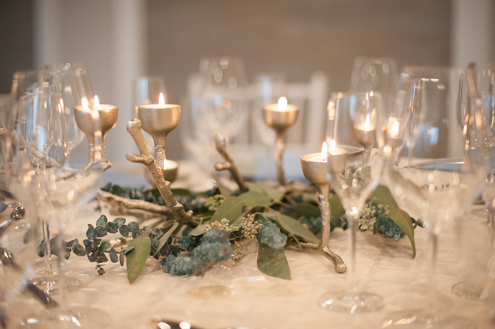Silver candelabras that resembled painted driftwood were set against pearlescent shells and dusty blue greenery.