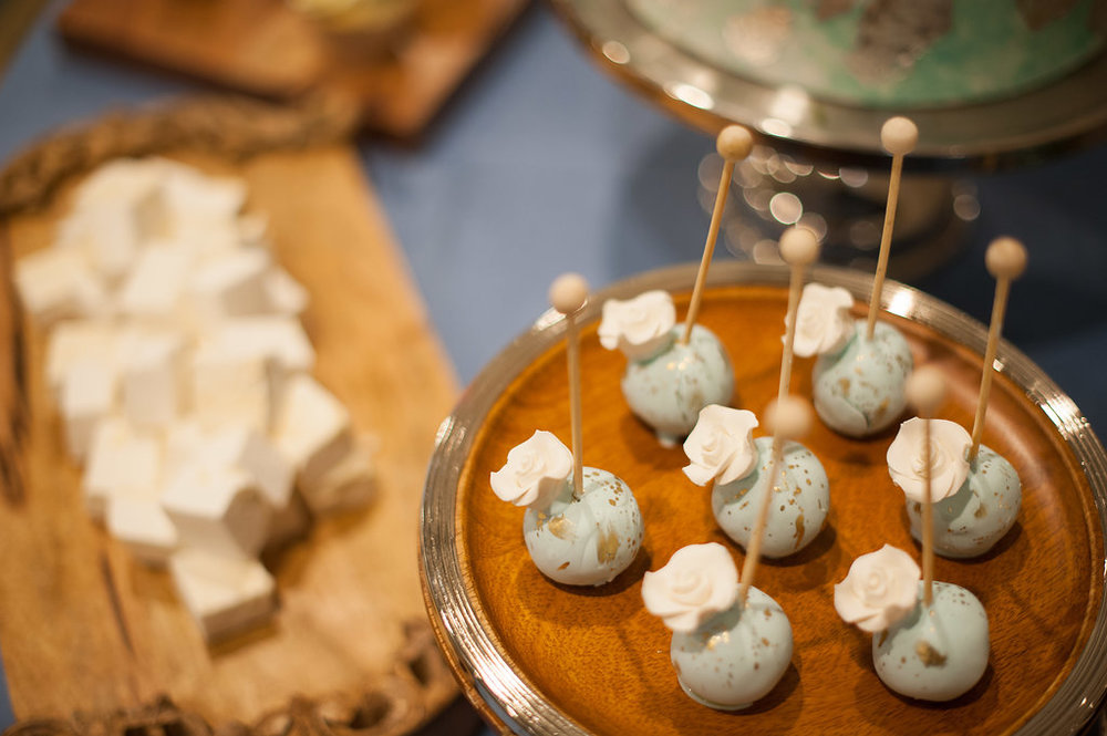 Cake pops the color of ocean foam were accented with metallic gold and ivory sugar roses. Sweet coastal chic!