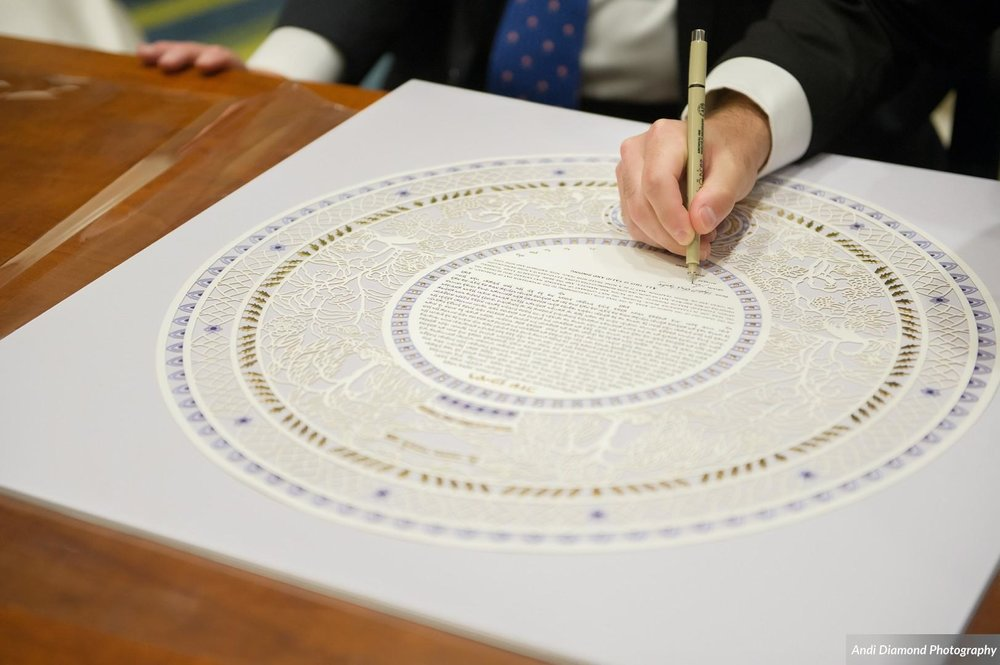 The groom signing the beautiful Ketubah, which outlines the promises he makes to his new wife.