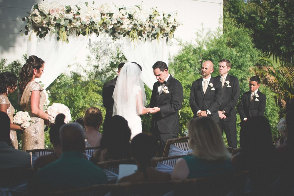 The couple exchanged vows during an outdoor ceremony beneath an arbor of flora and greenery, and a crystal chandelier.
