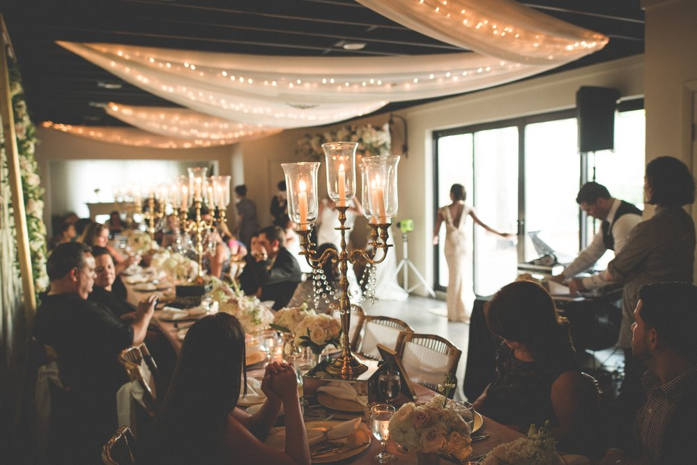 Elegant details, like drapery and twinkling lights strung overhead, as well as tables dressed with mirrored pedestals, gold and crystal candelabras, and clusters of blush and ivory roses, elevated this intimate wedding.
