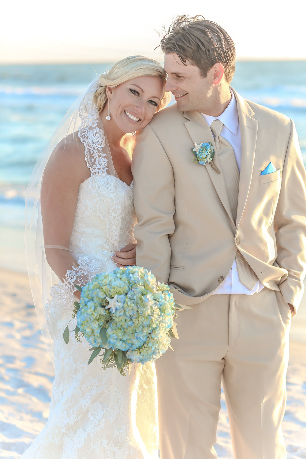 Elegantly styled in colors inspired by the beach, the couple look stunning against the water at sunset.