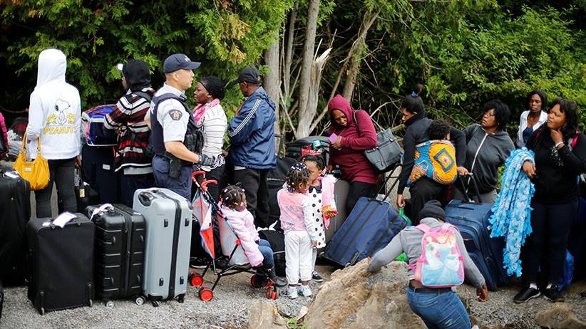 Migrants illegally crossing the border into Canada, assisted to carry their bags by the RCMP.