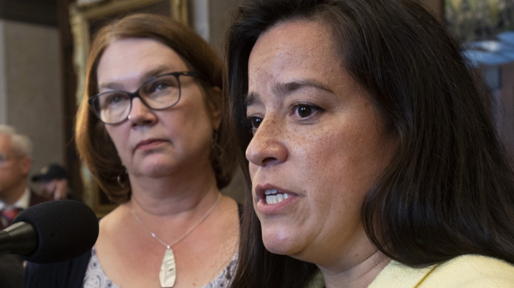 Jody Wilson-Raybould, and Jane Philpott in the background (notice the unbearable victimized bitch face). Photo credit: Canadian Broadcasting Cunts