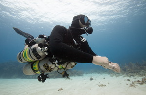 A TDI / PADI technical scuba diver is hovering up above a sandpatch while in decompression.  He attained his nitrox and trimix fills from coconut tree divers in roatan.
