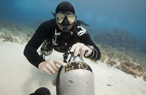 A sidemount techincal scuba diver with coconut tree divers and the roatan tec center is pointing with his finger to the max depth for the nitrox cylinder.