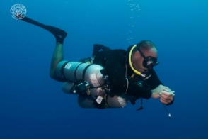 A technical sidemount diver reading his shearwater multigas computer while in decompression.  He is assisted by a sidemount photographer from coconut tree divers in roatan,