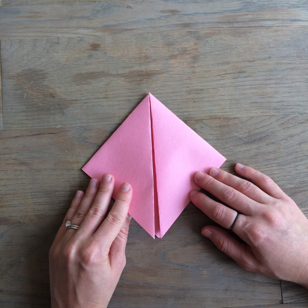 Step 4:  Fold corners to center point as shown, then open back up to original triangle.