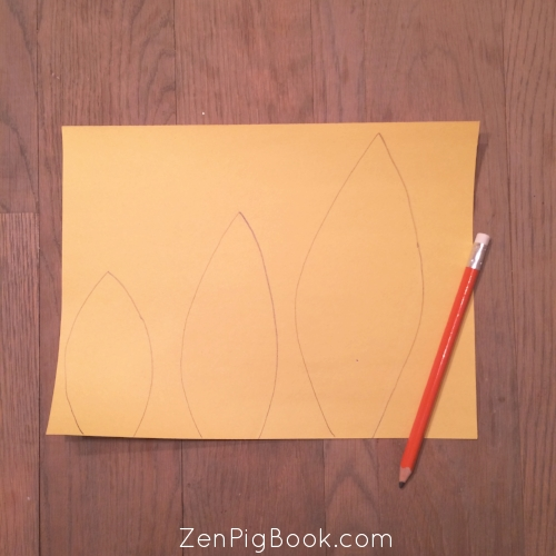 First, draw a small, medium, and large feather on each piece of construction paper.