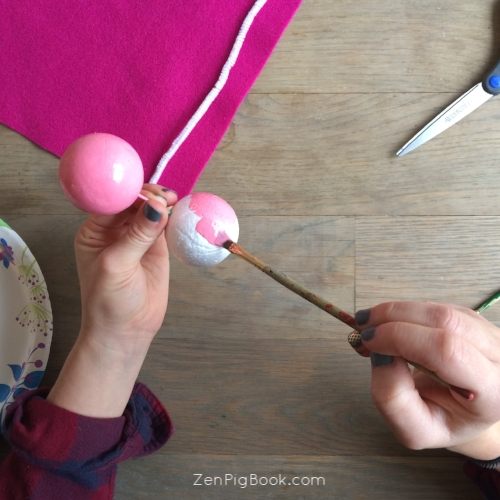 2.  Grab your paintbrush and paint each ball with the light pink paint. Put to the side and allow to dry.