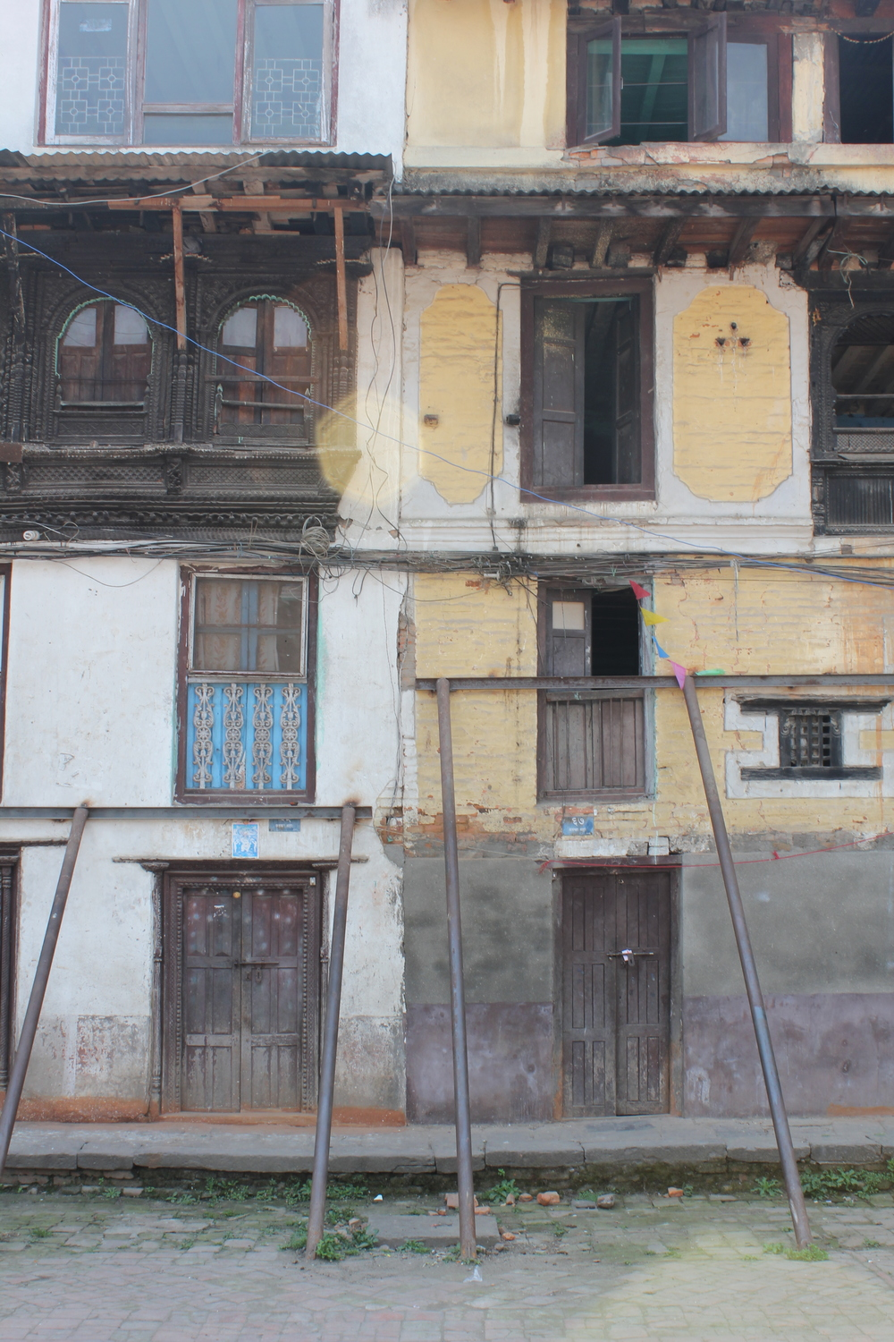 Steel beams used to support this housing structure in Kathmandu because of structural damage caused by the April 2015 earthquake.  A common sight in and around Kathmandu.
