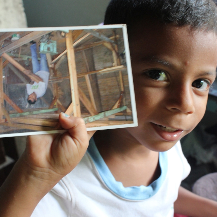 Isaac with a picture of his father Huber building one of their many looms with reclaimed wood from around their town
