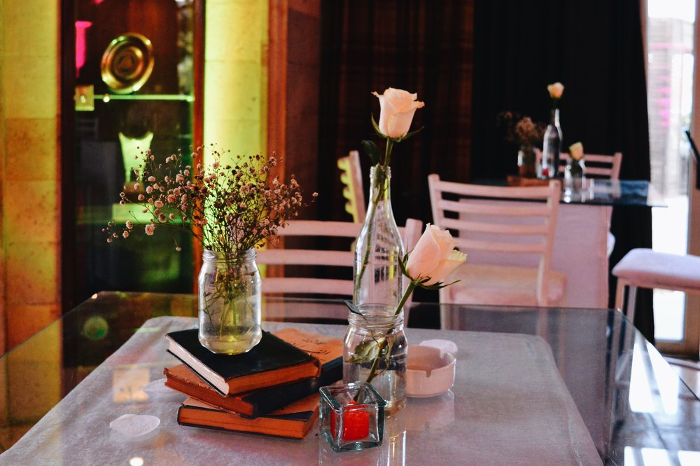 Another high table with stacked old vintage books and water filled jars with baby flowers and roses