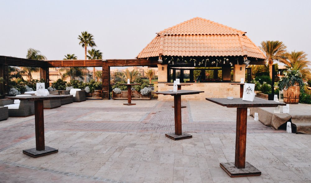 Lounges, high tables, bar and stage for an outdoor sunset ring reception